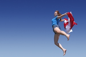 Girl jumping with the Canadian flag against backdrop of blue sky