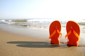A pair of orange flip flops stuck into a beach