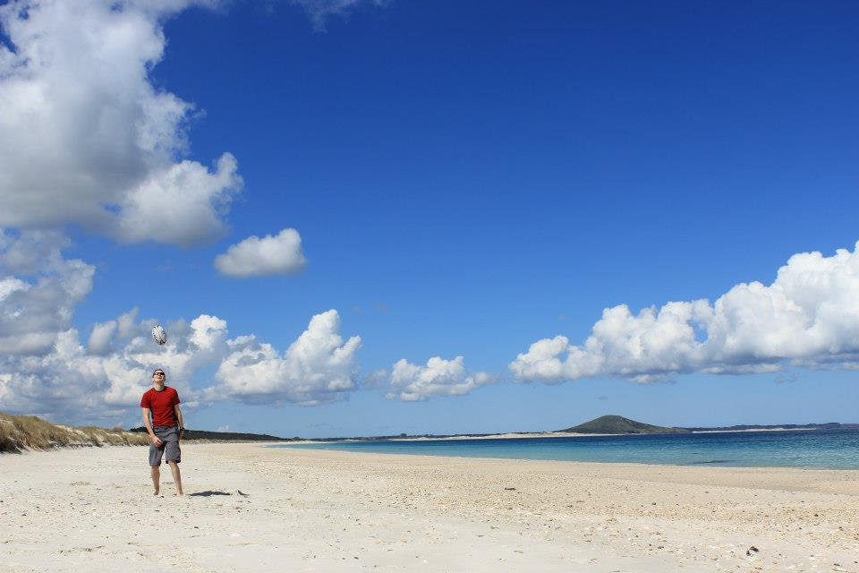 Karikari beach Northland New Zealand blue skies white sand and a man in a red top throwing a rugby ball