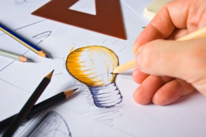 Photo showing a hand sketching a lightbulb surrounded by pencils